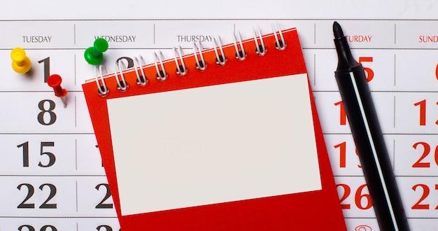 Há um bloco de notas vermelho e um marcador preto na superfície do calendário. em um bloco de notas, há um cartão branco em branco com um local para inserir texto