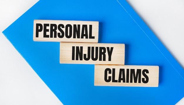Há um caderno azul sobre um fundo cinza claro. acima estão três blocos de madeira com as palavras reclamações de lesões pessoais.