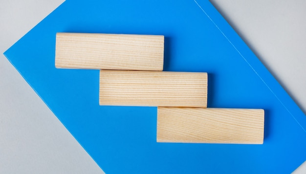 Há um caderno azul sobre um fundo cinza claro. no topo estão três blocos de madeira em branco com espaço para inserir texto. modelo. copie o espaço