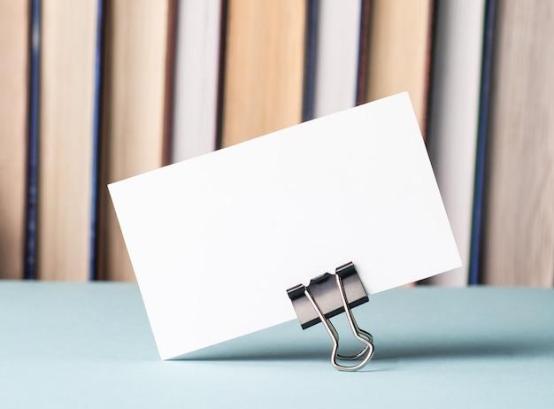 Há um cartão branco em branco com um local para inserir texto na mesa contra a superfície dos livros