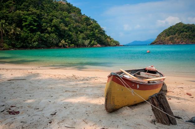 Há uma canoa laranja na areia.