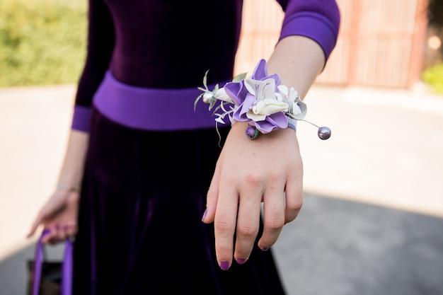 Há uma pulseira floral brilhante no pulso da menina