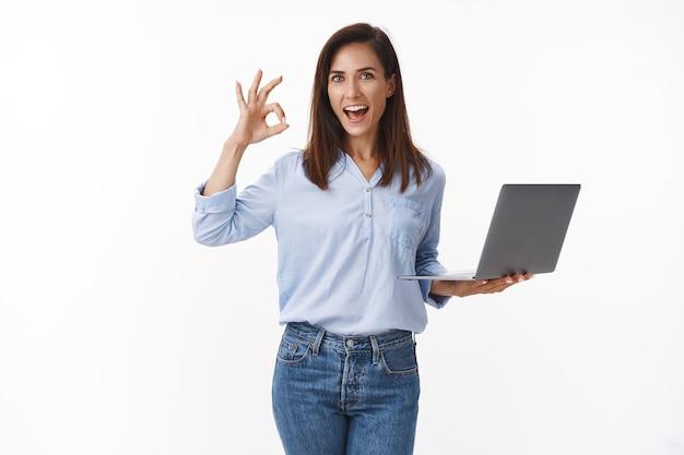 Habilidosa e bonita empreendedora profissional, segure laptop, mostre tudo bem, nenhum sinal de problema, sorrindo amplamente, lide com o programa ruim, assegure ao cliente que está tudo bem, fique de pé na parede branca confiante