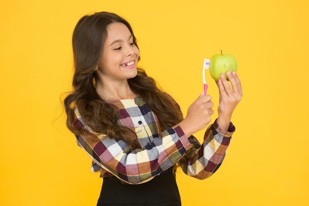 Hábitos saudáveis. criança pequena com maçã de escova de sorriso saudável. boa higiene oral. mantenha os dentes e as gengivas saudáveis. comida amigável com os dentes. alimentação saudável. educação em saúde bucal.