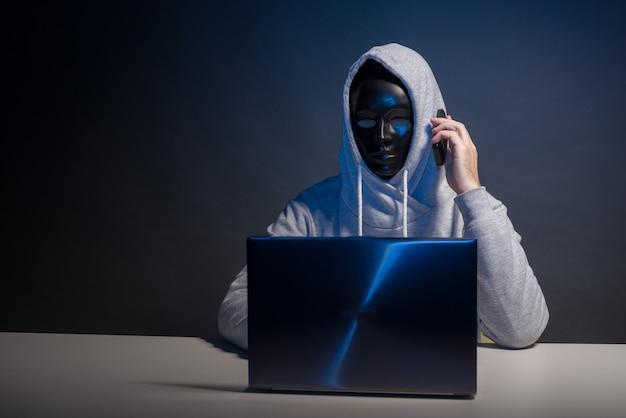 Hacker anônimo em programador de máscara usa um laptop e fala ao telefone para hackear o sistema no escuro. o conceito de cibercrime e banco de dados de hacking