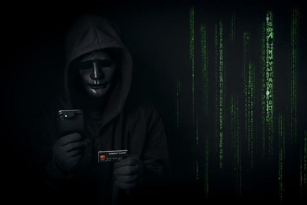 Hacker anônimo perigoso com capa e máscara usa smartphone e cartão de crédito