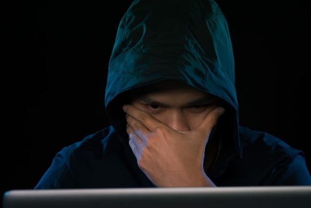 Hacker asiático hackeando a rede de computadores com o laptop no escuro. conceito de segurança cibernética