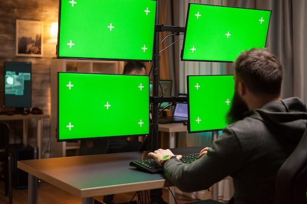 Hacker barbudo espalhando um vírus usando telas verdes de computador.