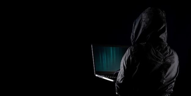 Hacker cibercriminoso encapuzado usando laptop para hackear internet no ciberespaço, mas com fundo preto, conceito de segurança de dados pessoais de internet.