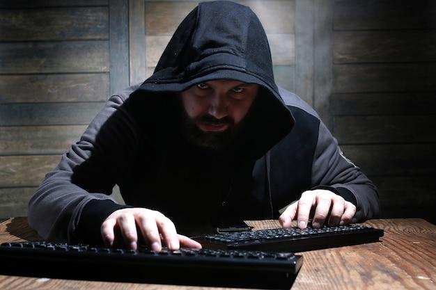 Hacker com capô preto em uma sala com paredes de madeira