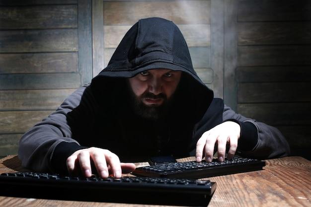 Hacker com capuz preto em uma sala com paredes de madeira
