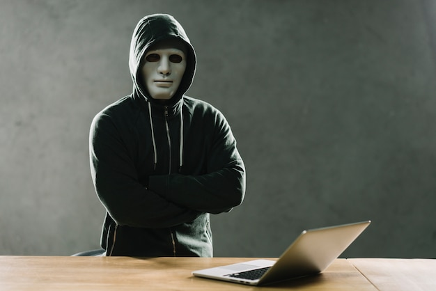 Hacker com laptop na mesa