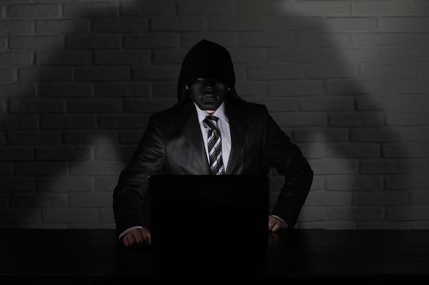 Hacker com máscara preta e capuz na mesa em frente ao monitor