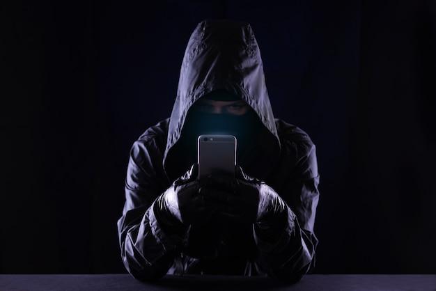 Hacker de crime cibernético encapuzado usando internet do telefone móvel invadindo o ciberespaço, o conceito de segurança de dados pessoais online.