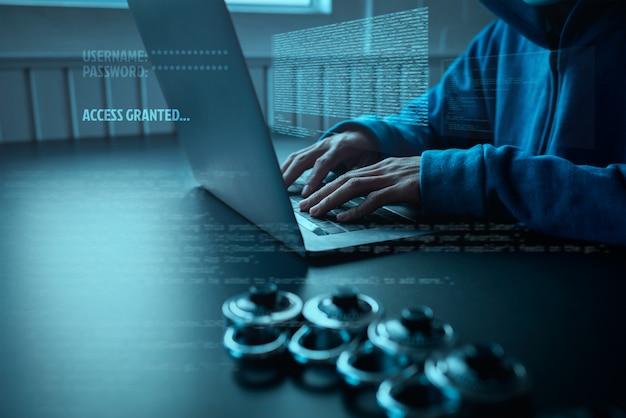 Hacker de povos asiáticos usa uma máscara usando um ataque cibernético de laptop.