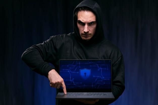Hacker de tiro médio segurando laptop