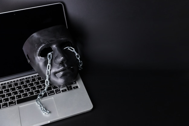 Hacker e conceito de crime cibernético, máscara preta com corrente no novo computador em fundo preto