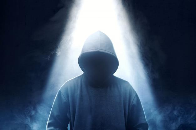Hacker em pé de capuz preto com fumaça e luz de cima
