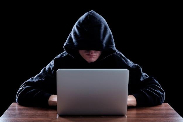 Hacker em um casaco com capuz escuro, sentado na frente de um notebook