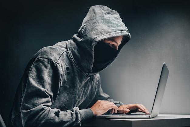 Hacker encapuzado com rosto oculto acessando informações pessoais no laptop no escuro