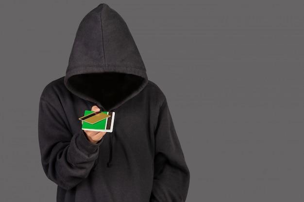 Hacker está carregando um cartão de crédito dourado e uma carteira bancária