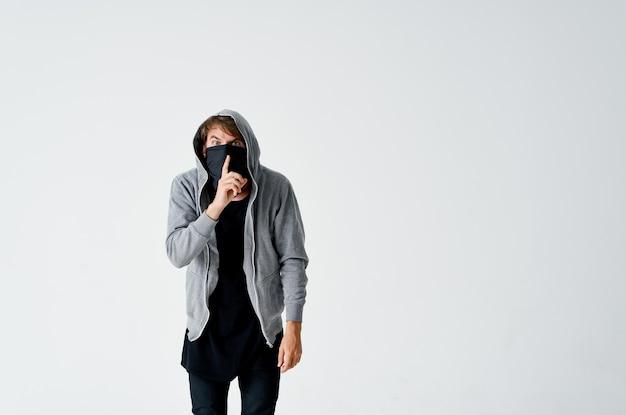 Hacker masculino com máscara preta e capuz em um roubo de espaço leve