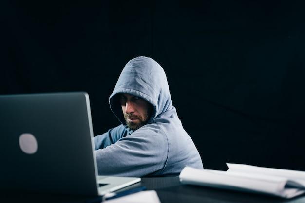 Hacker misterioso de barbudo esconde o rosto sob o capô, fazendo algo ilegal no laptop