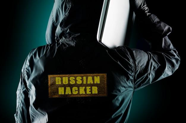 Hacker russo com um laptop no ombro em um fundo escuro. o conceito de risco dos hackers russos em questões políticas de países europeus e americanos