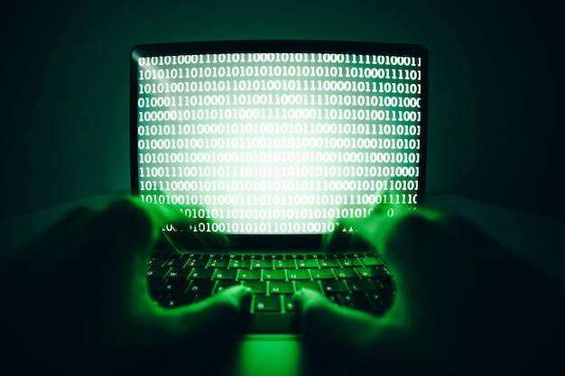 Hacker usando o laptop para codificar vírus ou malware para hackear servidor de internet