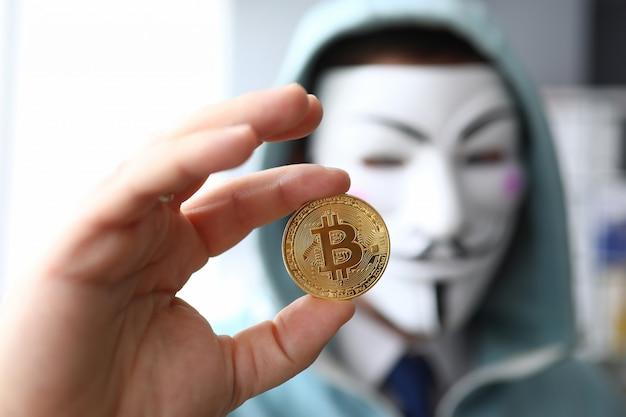 Hacker usar máscara anonymus segurar bitcoin na mão