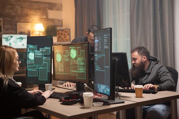 Hackers organizados em uma sala com computadores que roubam informações online.