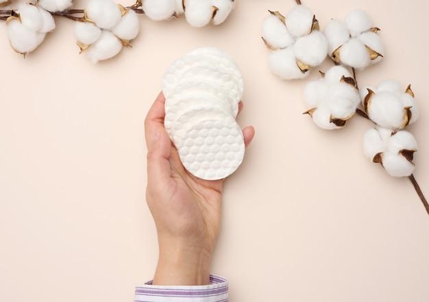 Hadn segurando esponjas de algodão brancas sobre fundo bege. design para a indústria de beleza, medicina e cosméticos