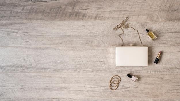 Hairbands; frasco de perfume; batom e verniz de unhas com embreagem branca no pano de fundo texturizado de madeira