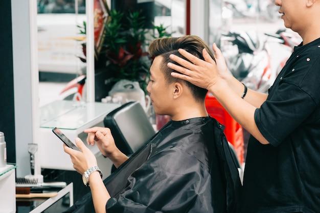 Hairstylist cortado que dá o toque final ao hairdo do cliente masculino