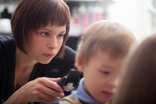 Hairstylist cortar um cabelo de meninos