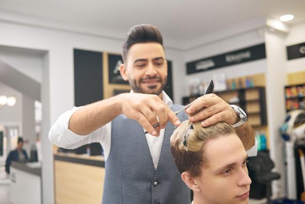 Hairstylist de sorriso que faz hairdress para o cliente novo no salão de beleza beaty.