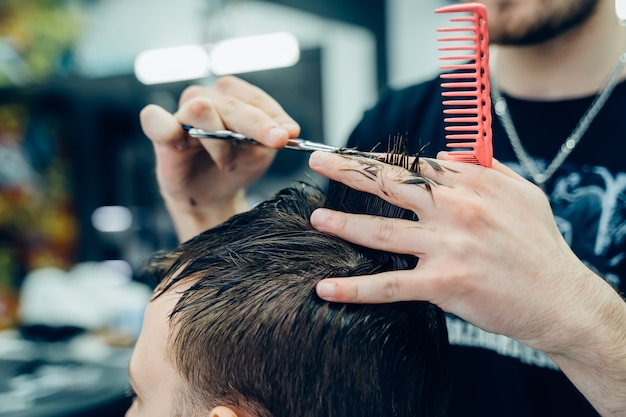 Hairstylist masculino que corta o cabelo de um cliente