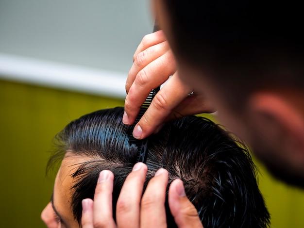 Hairstylist penteando o cabelo do cliente