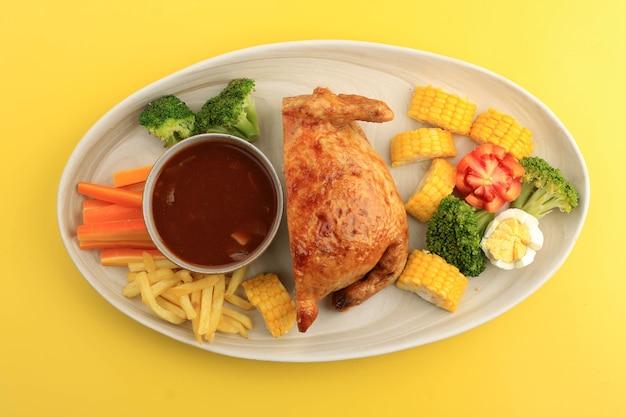 Half ayam kodok é frango inteiro recheado com carne e ovo, sirva com batatas fritas, brócolis e cenoura também molho de churrasco. isolado em fundo amarelo