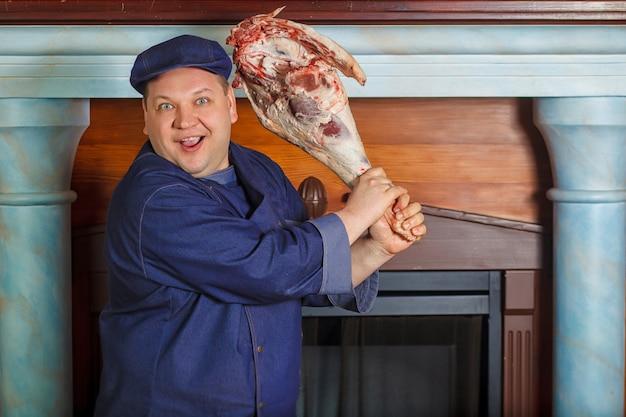 Half legth tiro do chef masculino pensativo, detém muito grande peça de carne vermelha crua