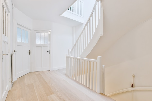 Hall com pavimento em madeira e paredes brancas com portas envidraçadas e escada para cima e para baixo