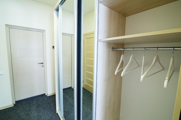 Hall de entrada longo e bem iluminado com portas em um hotel novo com guarda-roupa