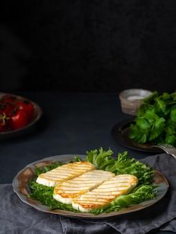 Halloumi grelhado, queijo frito com salada de alface. dieta equilibrada em fundo escuro, vista lateral