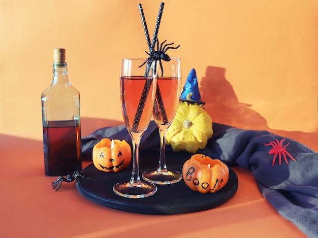Halloween bebe aranhas de abóboras de vinho e decoração mística em um fundo laranja brilhante