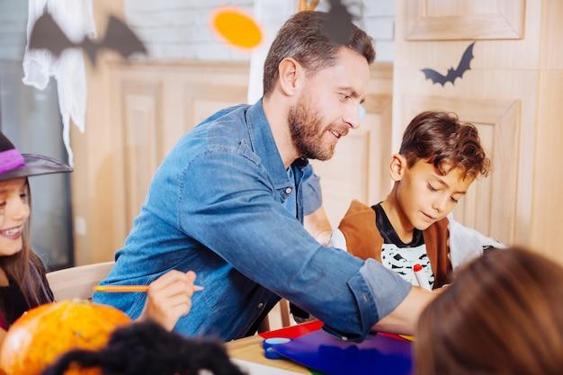 Halloween com crianças. pai prestativo sentindo-se extremamente memorável e feliz por comemorar o halloween com seus filhos Foto Premium