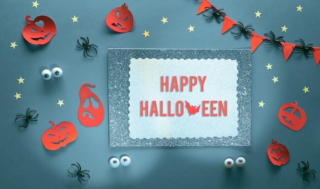 Halloween criativo plana leigos em roxo, laranja, prata e preto. vista superior em morcegos de artesanato de papel e abóboras de lanterna jack, estrelas, olhos de chocolate e aranhas. cópia-espaço em papel brilhante.