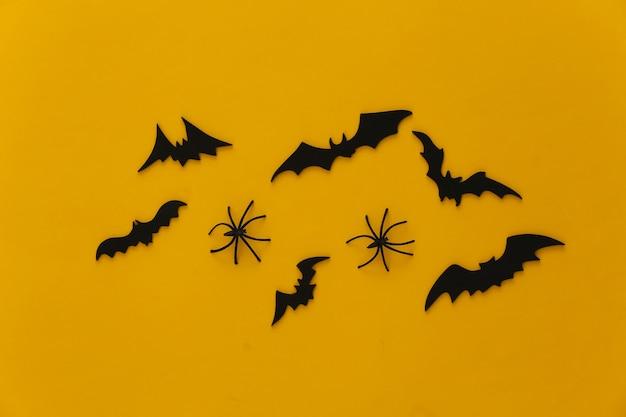 Halloween, decorações e conceito assustador. aranhas e morcegos pretos voam sobre o amarelo