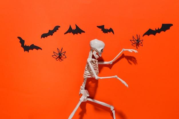 Halloween, decorações e conceito assustador. esqueleto e aranhas, morcegos pretos voam sobre laranja brilhante