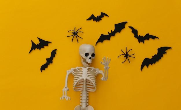 Halloween, decorações e conceito assustador. esqueleto e aranhas, morcegos pretos voam sobre o amarelo