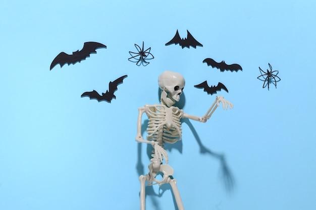 Halloween, decorações e conceito assustador. esqueleto e aranhas, morcegos pretos voam sobre o azul brilhante